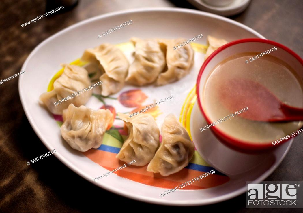 Stock Photo: Close-up of dumplings with a bowl of soup.