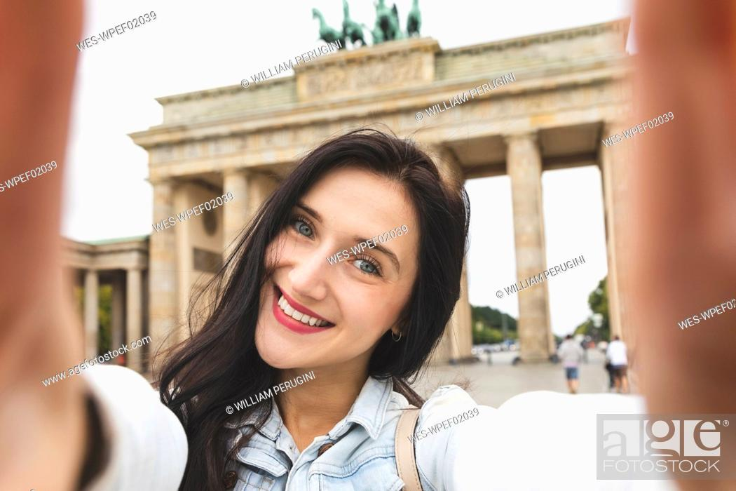 Stock Photo: Selfie of happy young woman at Brandenburg Gate, Berlin, Germany.