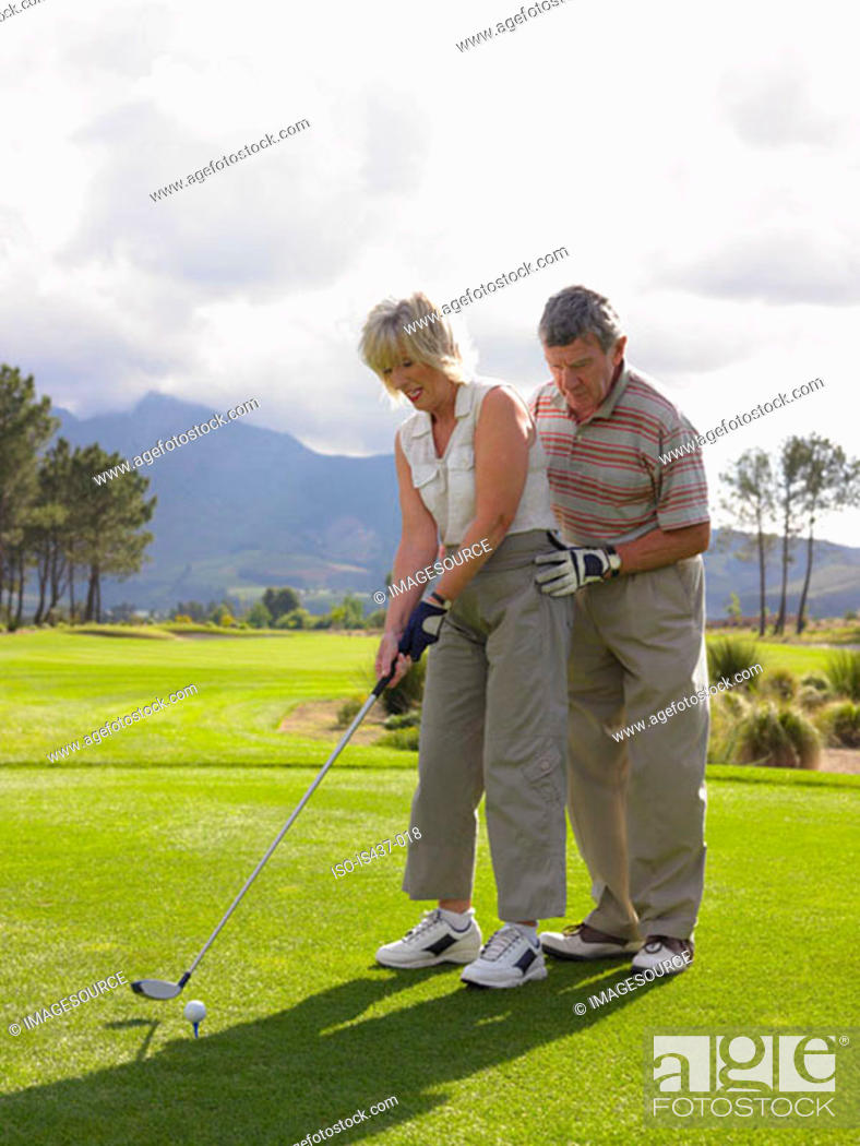Stock Photo: Man giving woman a golf lesson.
