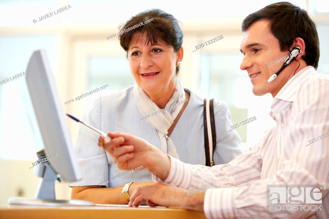Stock Photo: Office worker giving information to retired woman.