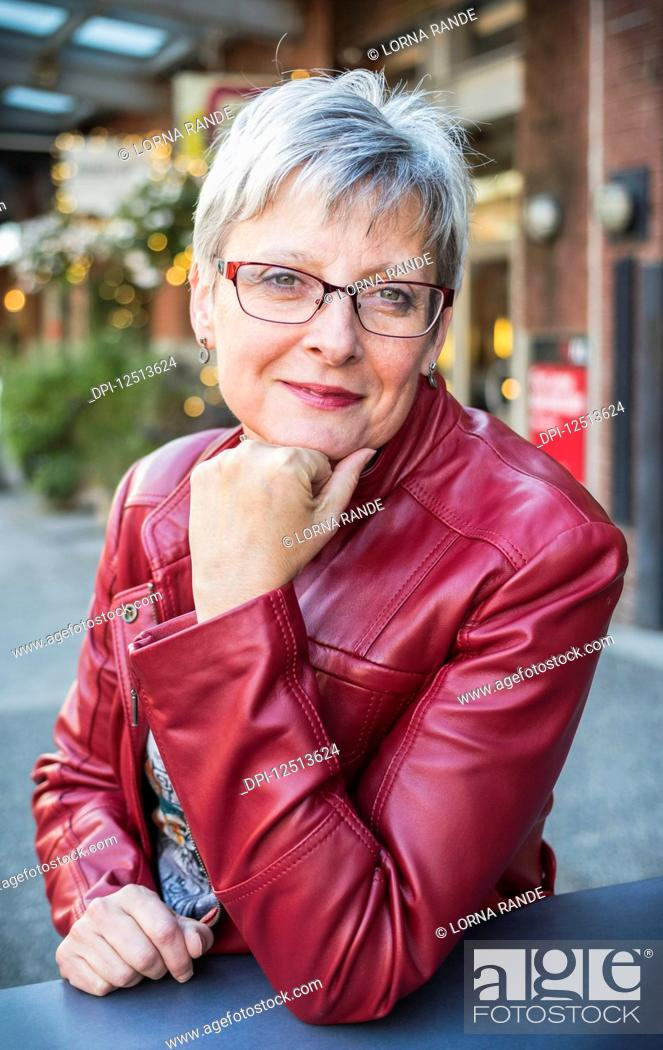 Stock Photo: Portrait of a mature woman in a red leather jacket sitting at a table with her chin resting in her hand; Vancouver, British Columbia, Canada.
