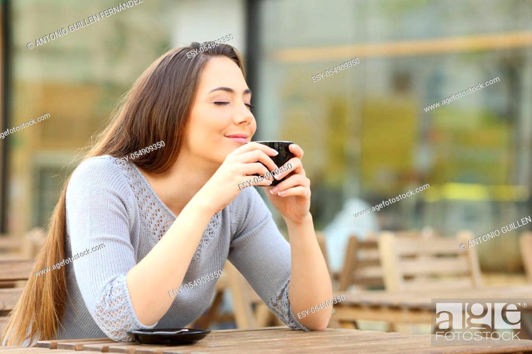 Stock Photo: Satisfied woman smelling her cup of coffee on a restaurant terrace.