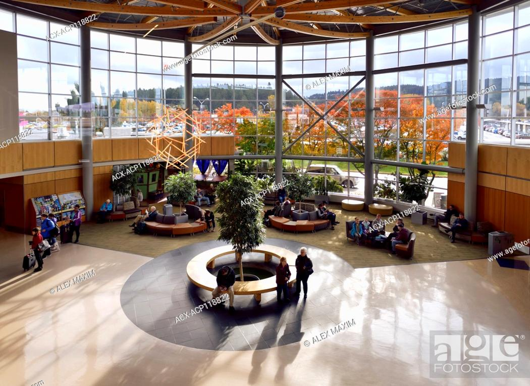 Imagen: People in a waiting lounge of Victoria International Airport YYJ, lobby interior with beautiful colorful autumn trees outside.