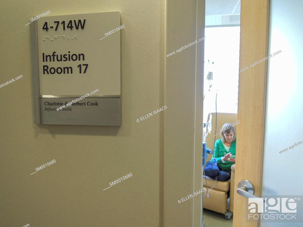 Stock Photo: Caucasian woman seen through the door of a hospital infusion room getting a chemotherapy drug treatment for cancer.
