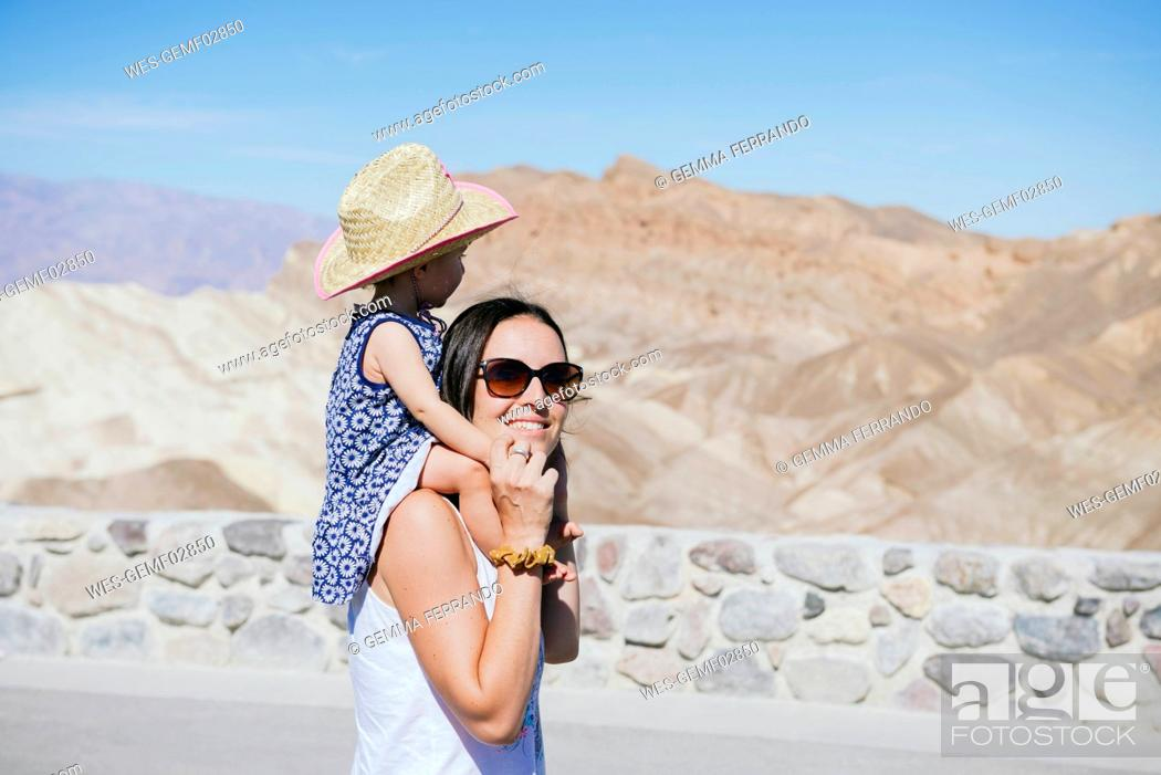 Stock Photo: USA, California, Death Valley National Park, Twenty Mule Team Canyon, smiling mother carrying baby girl.