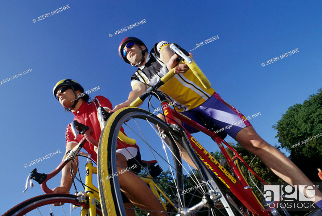 Stock Photo: Two young men 15-20 20-25 25-30 years old, sportsmen, bikers, cyclists, cycling outside in summer.