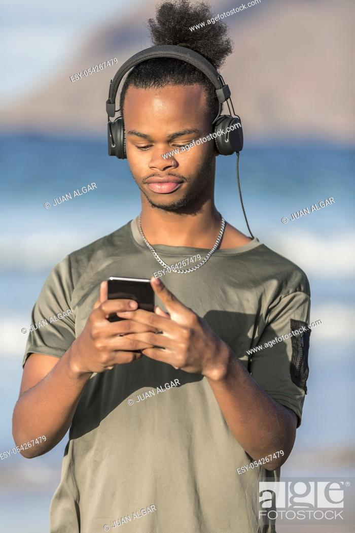 Stock Photo: Handsome African American guy in modern headphones browsing smartphone and listening to music while standing on blurred background of sea.