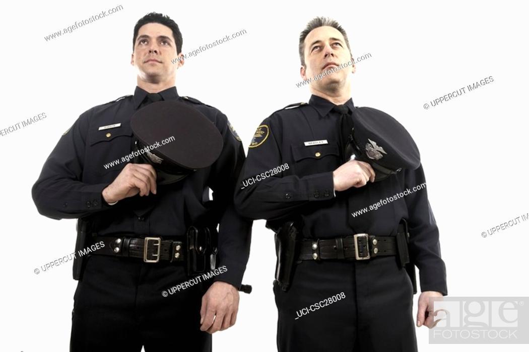 Stock Photo: Male police officers holding their hats over their chest.