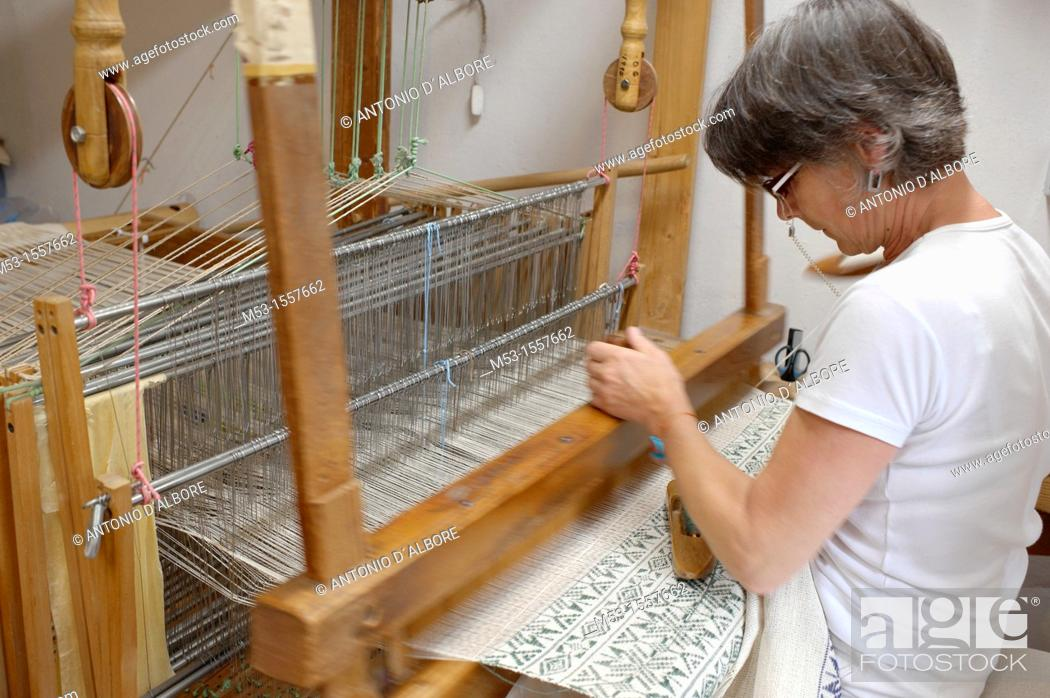 Stock Photo: A female professional weaver operating an old loom making a fabric with traditional design carpet at Arteler workshop Mezzano di Primiero, Italy.