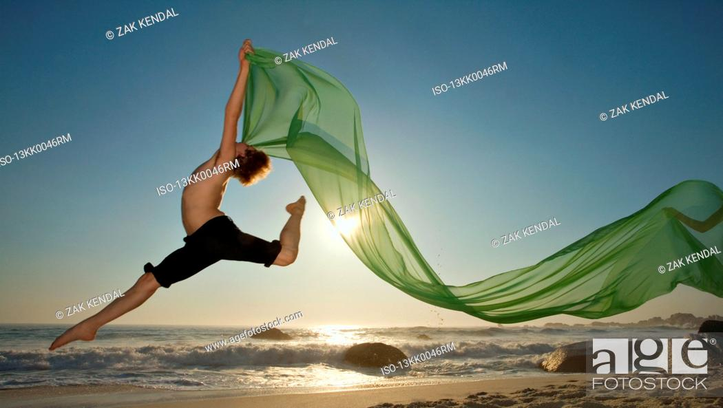 Stock Photo: Dancer leaping on a beach.