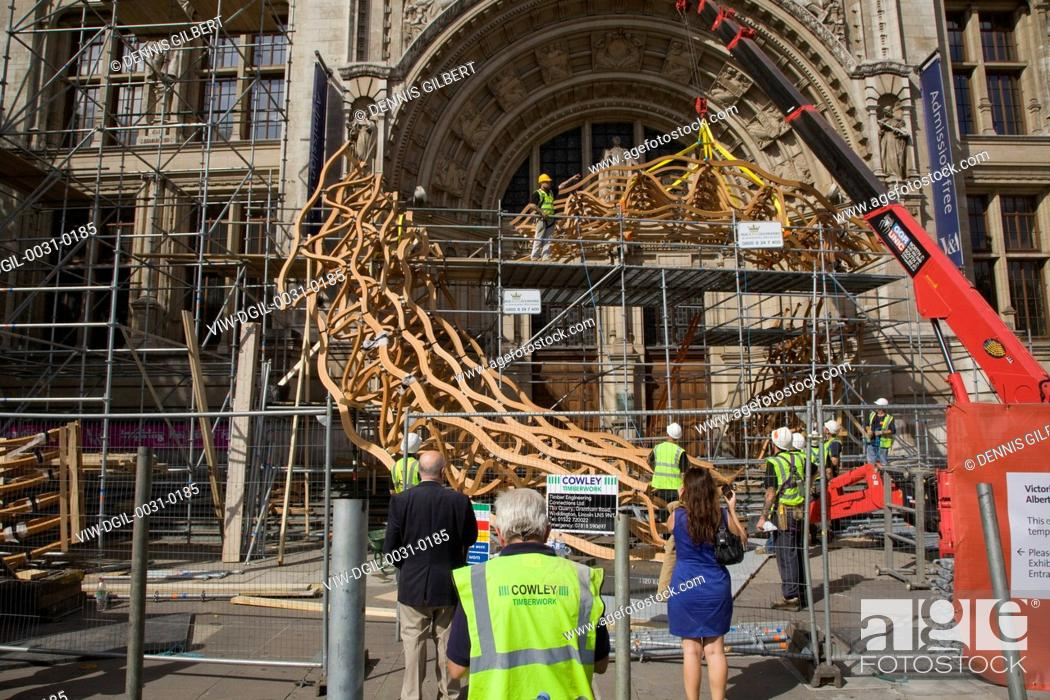 Stock Photo: Timber Wave, Installation for London Design Festival 2011, London, United Kingdom. Architect: AL-A, 2011. Sculpture under construction with passersby.