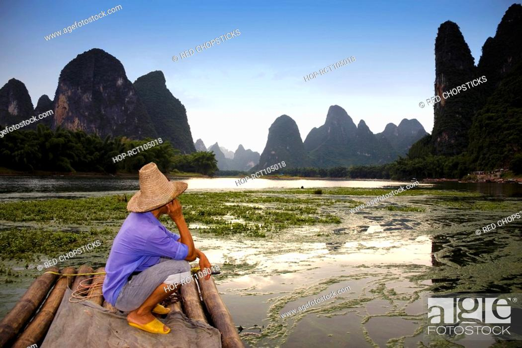 Stock Photo: Side profile of a mature man crouching on a bamboo raft with a hill range in the background, Guilin Hills, XingPing, Yangshuo, Guangxi Province, China.