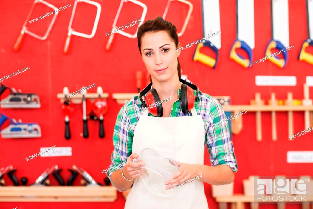 Stock Photo: Female carpenter in front of wood work tools, portrait.
