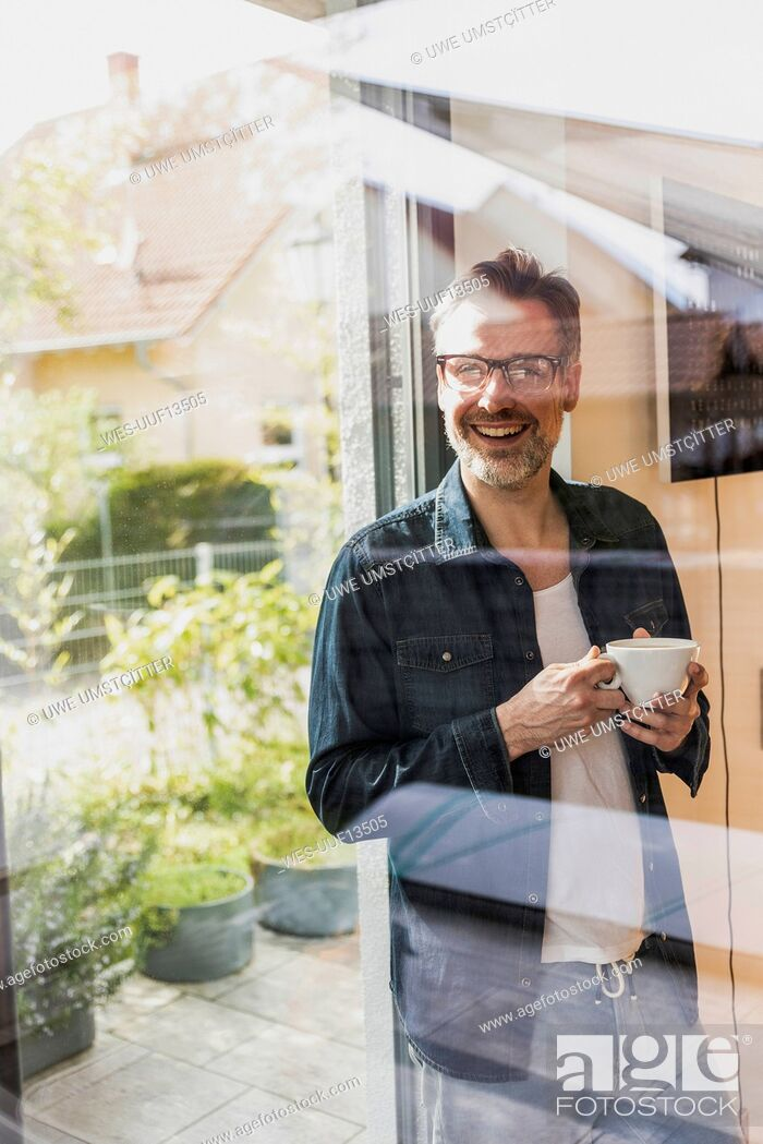 Imagen: Portrait of laughing man with cup of coffee standing behind glass door at home.