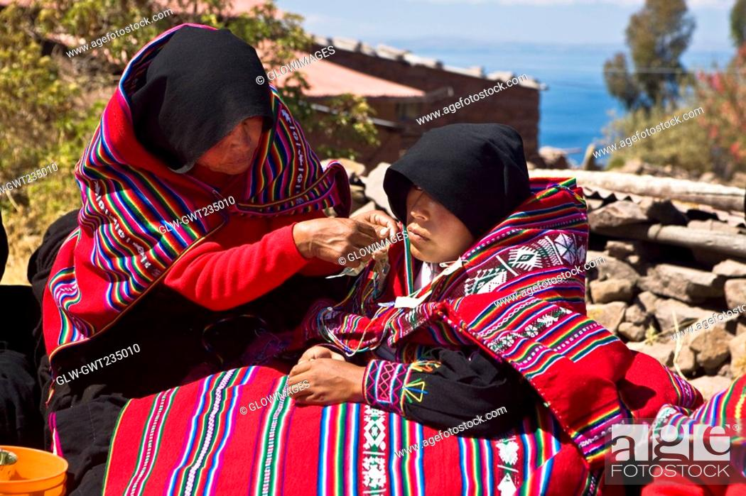 Stock Photo: Mid adult woman grooming a bride for wedding, Taquile Island, Lake Titicaca, Puno, Peru.