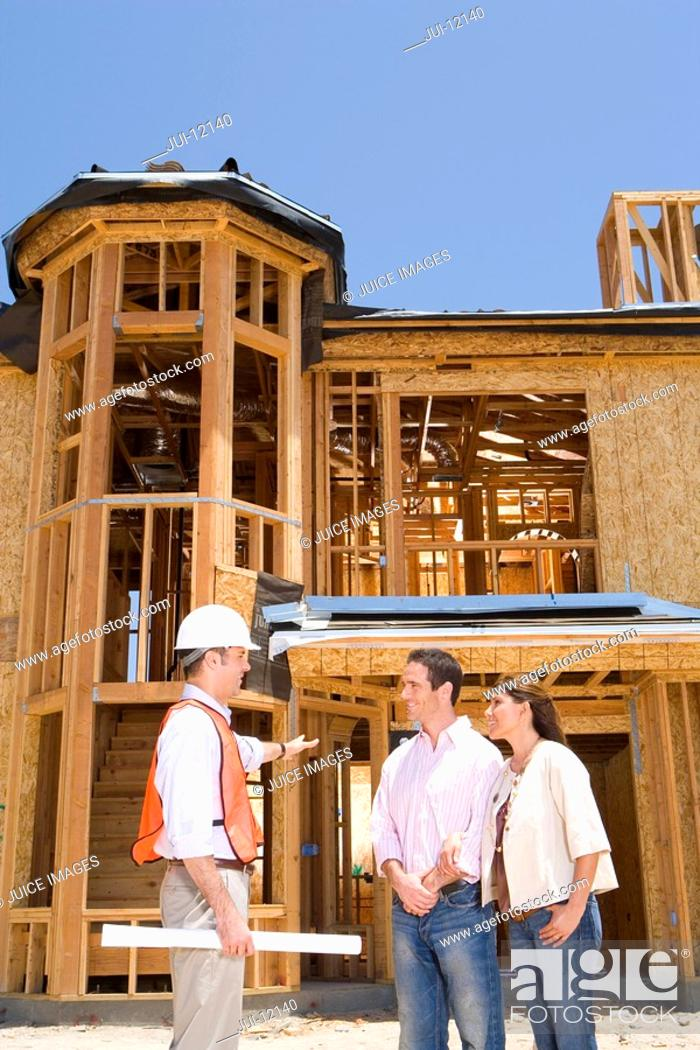 Stock Photo: Young couple in conversation with architect in front of partially built house, side view.
