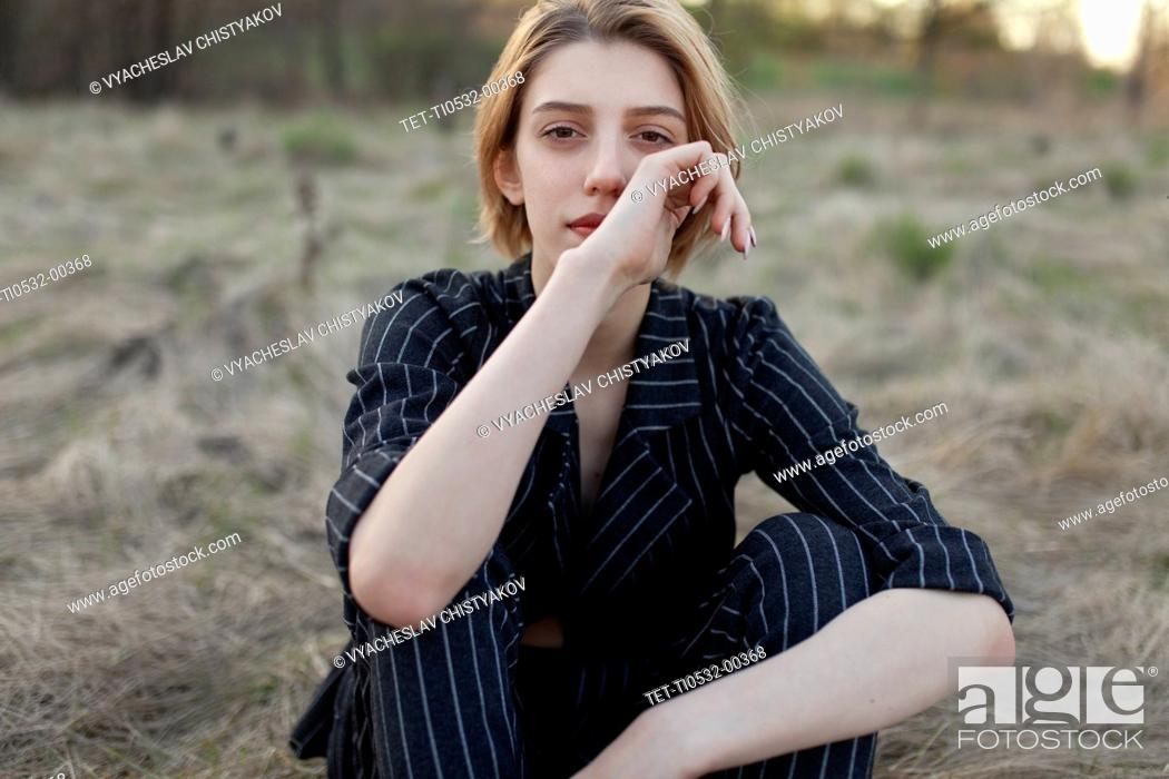 Photo de stock: Russia, Omsk, Portrait of young woman sitting in grass.