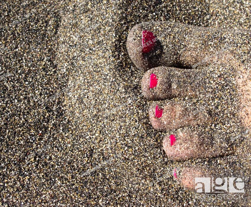 Stock Photo: Woman feet half-buried in the sand.