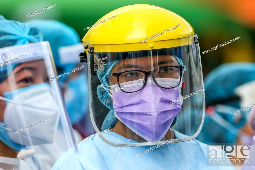 Stock Photo: (200511) -- MANILA, May 11, 2020 (Xinhua) -- Nurses wearing protective equipment are seen at a triage area as they wait for patients outside a hospital in.