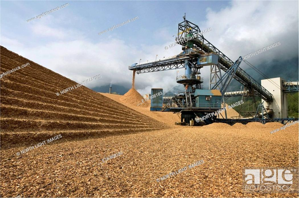Stock Photo: Canada, BC, Port Mellon.  Wood chip pile and conveyor at pulp and paper mill.