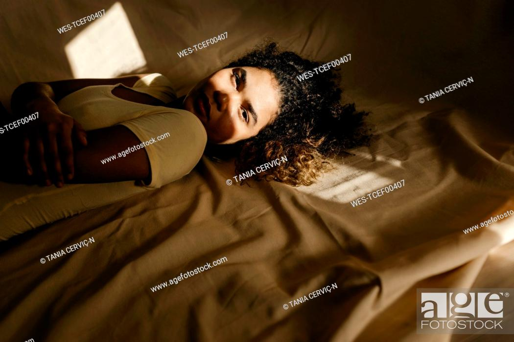 Stock Photo: Portrait of attractive young woman lying in bed in sunlight.