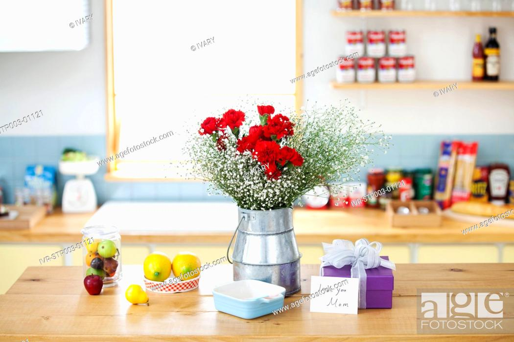 Stock Photo: Wrapped Gift Box And Bunch Of Flower On The Kitchen Counter.