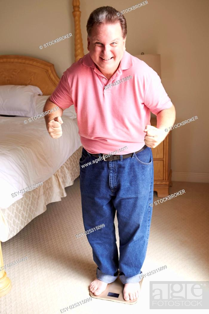 Stock Photo: Happy Overweight Man Standing On Scales In Bedroom.