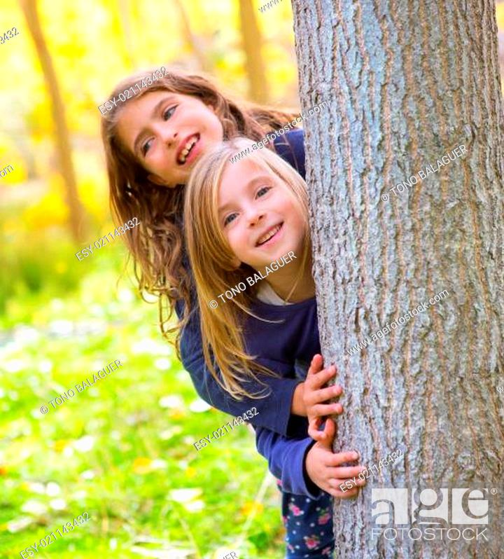 Stock Photo: Autumn sister kid girls playing in forest trunk outdoor.