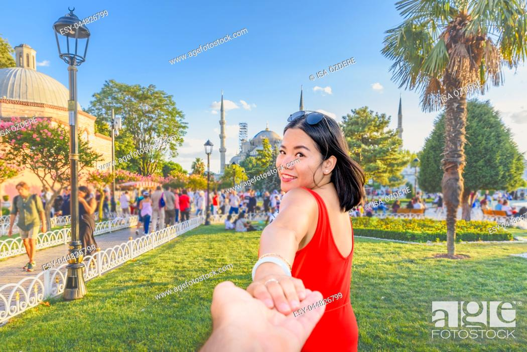 Imagen: Beautiful woman poses with view of Sultanahmet or Blue Mosque on background in Istanbul, Turkey. Follow me concept.