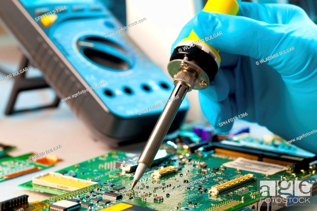 Stock Photo: Soldering microchip on to a printed circuit board.