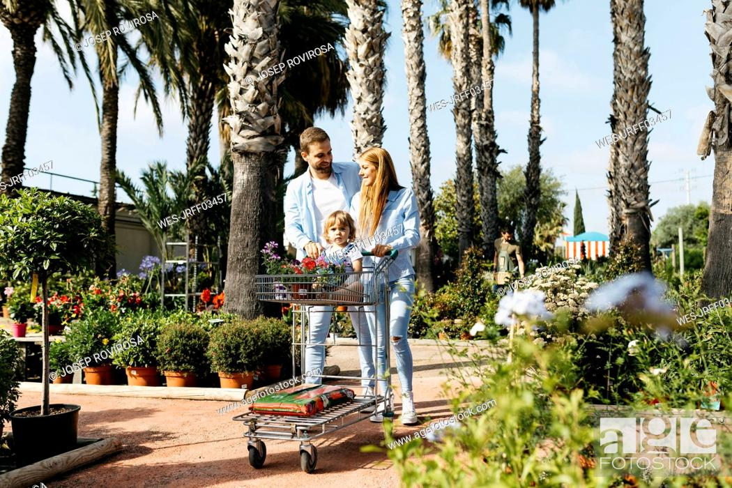Stock Photo: Happy family buying plants in a garden center wth the daughter in shopping cart.