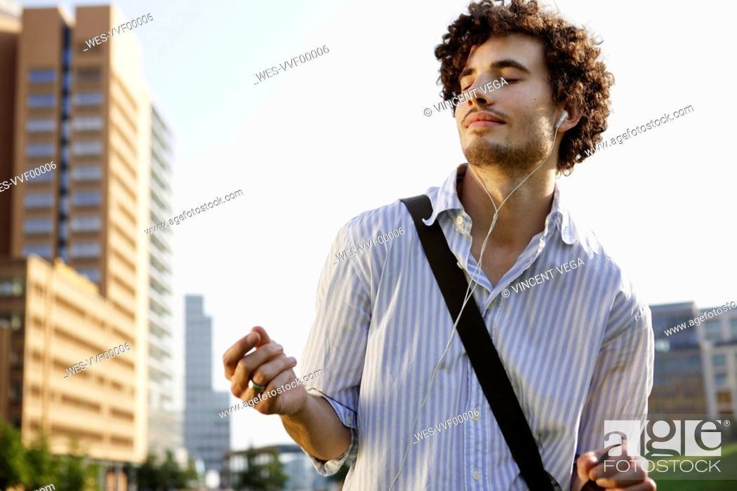 Stock Photo: Germany, Berlin, Young man wearing earphones, dancing, portrait, close-up.