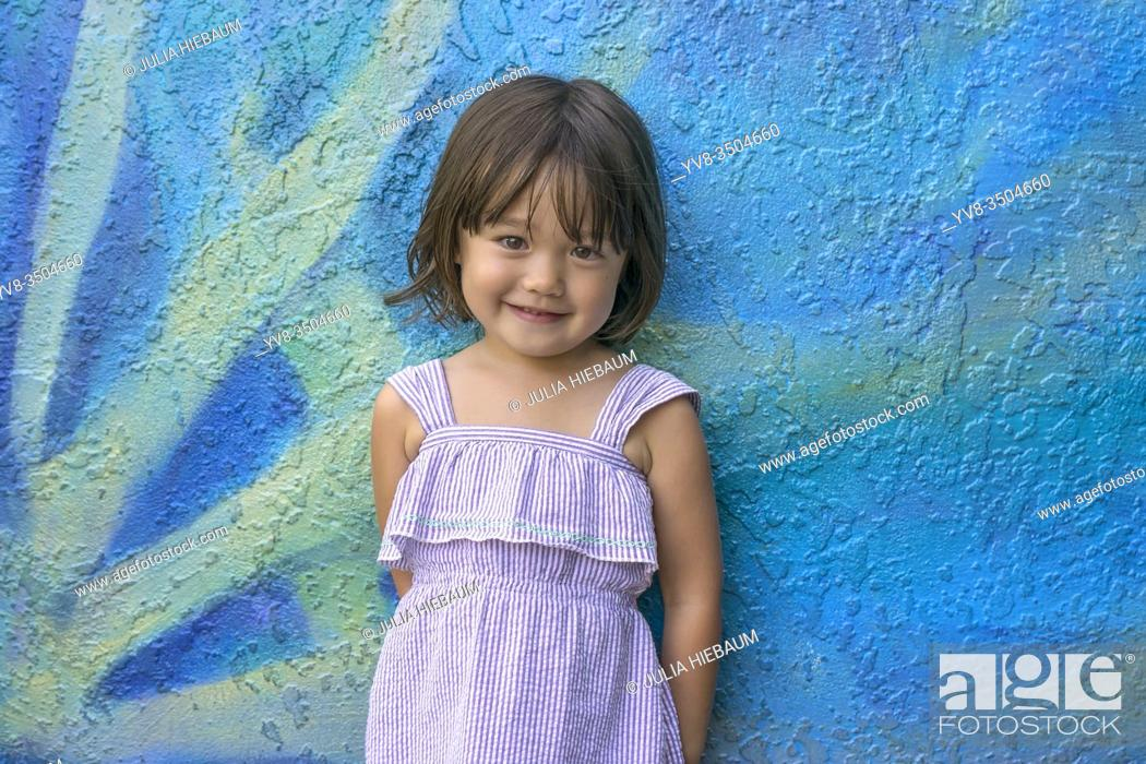 Stock Photo: Three year old girl standing in front of a colorful wall in San Diego, California.