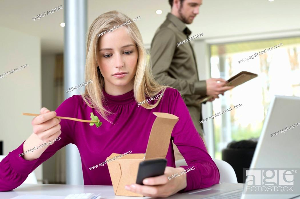 Stock Photo: Businesswoman eating salad while working in the home office.
