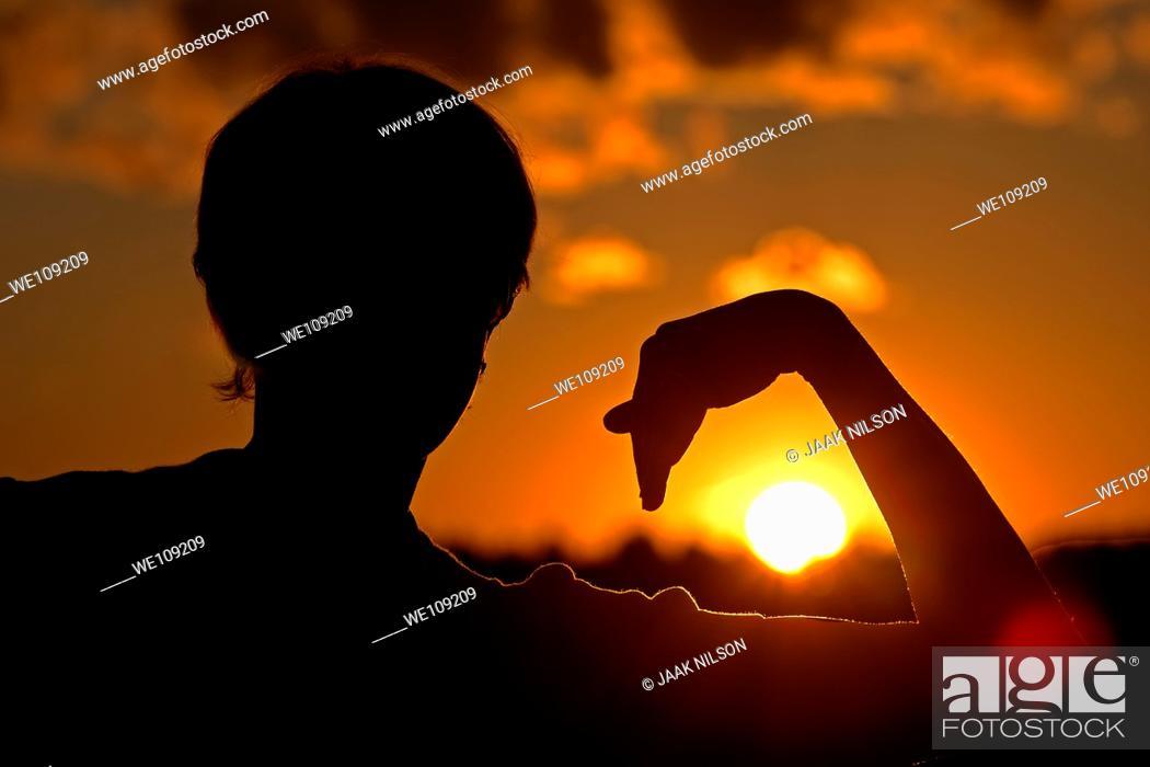 Stock Photo: Woman silhouette holding arm around sun.