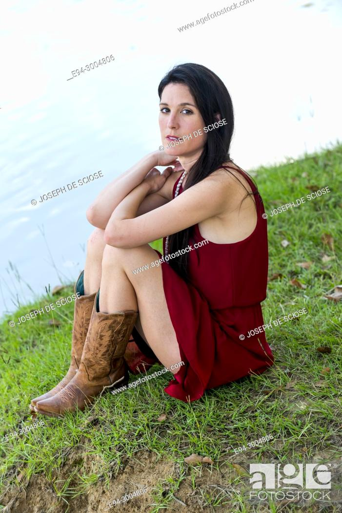 Photo de stock: A 39 year old brunette woman looking at the camera wearing a red dress and boots, sitting on grass next to a pond.
