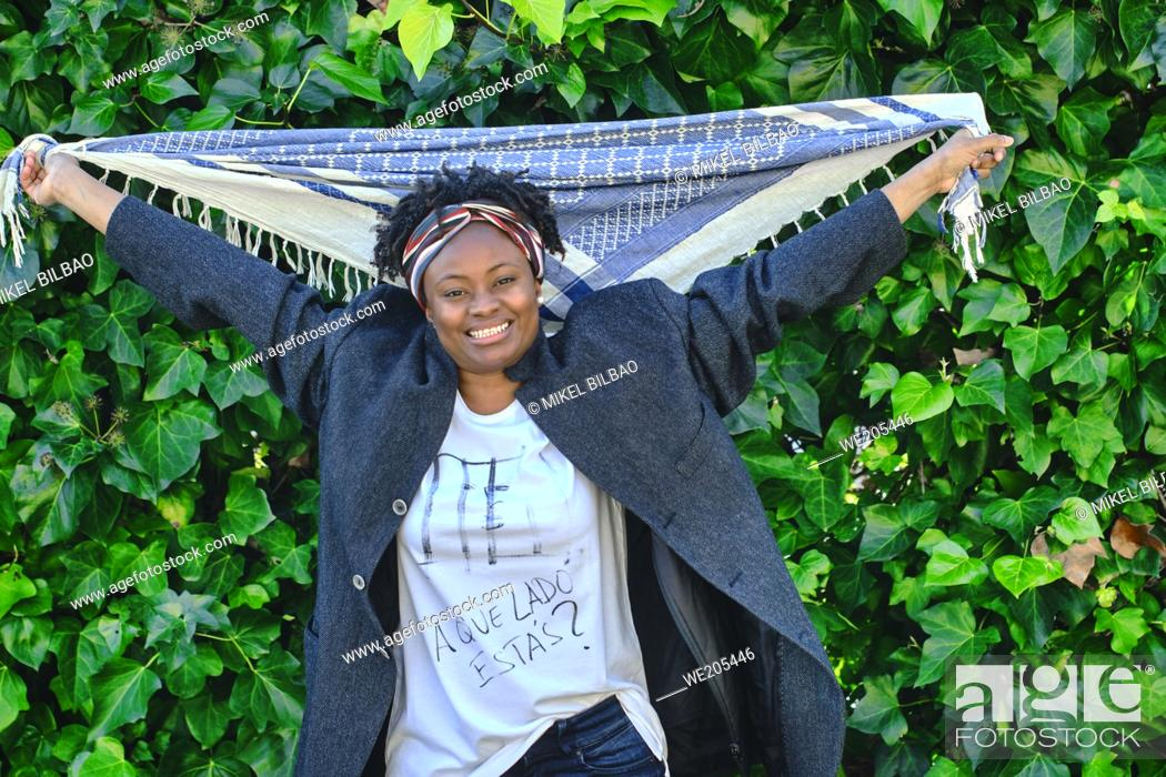 Imagen: Happy young african woman with an cool hair style and a t-shirt posing outdoor in a garden with a leaves background.