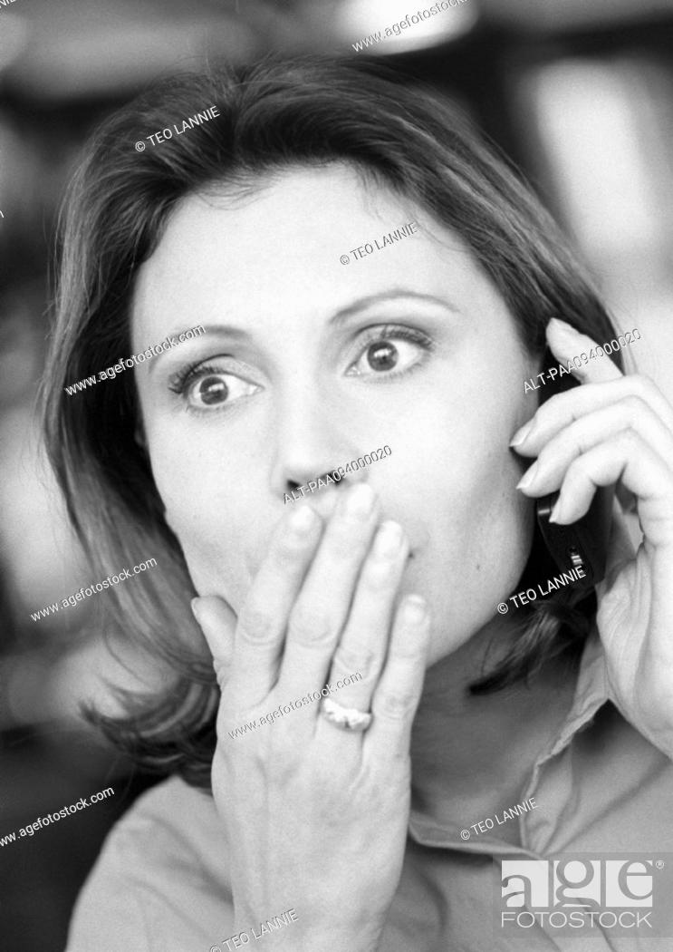 Stock Photo: Woman using cell phone, hand over mouth, close-up, B&W.