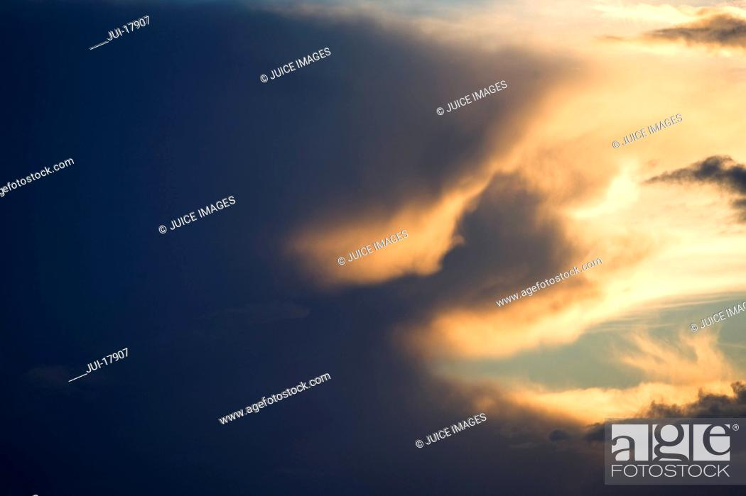 Stock Photo: Sun setting behind clouds in sky.