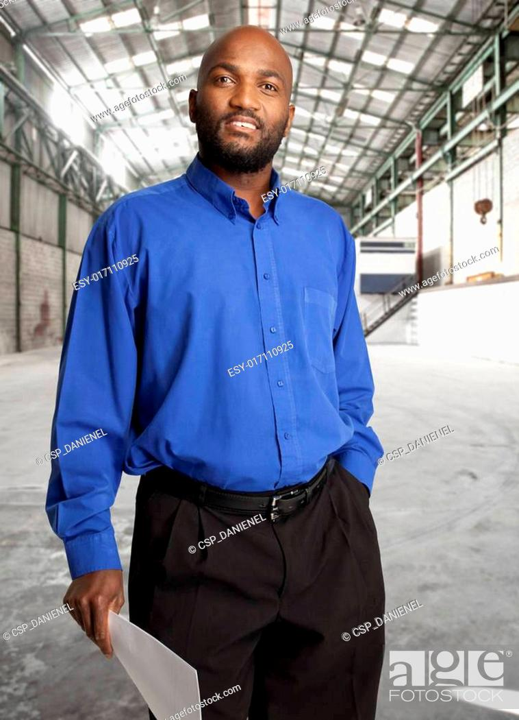 Stock Photo: African businessman in open warehouse space, holding a document.
