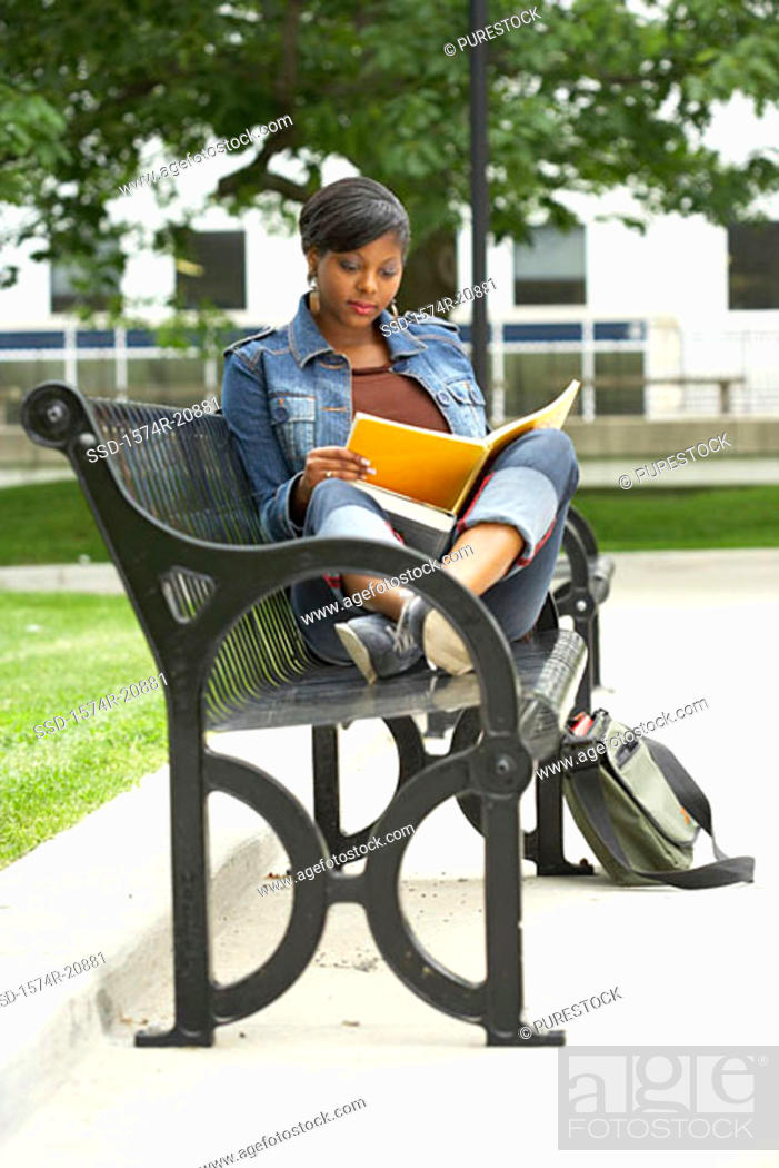 Stock Photo: College student sitting on a bench and reading a book.