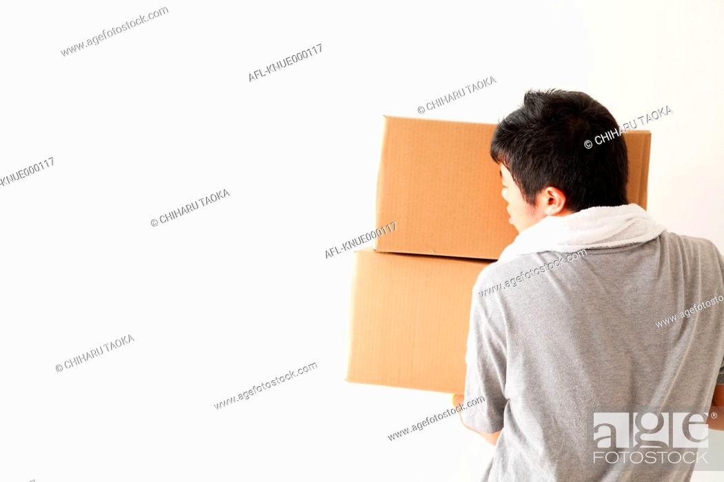 Stock Photo: Japanese man with heavy boxes.