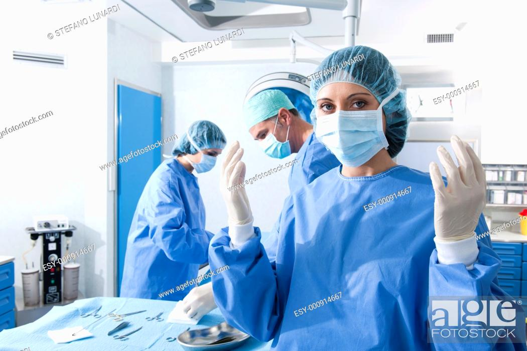 Stock Photo: Portrait of a female surgeon, operation in the background.