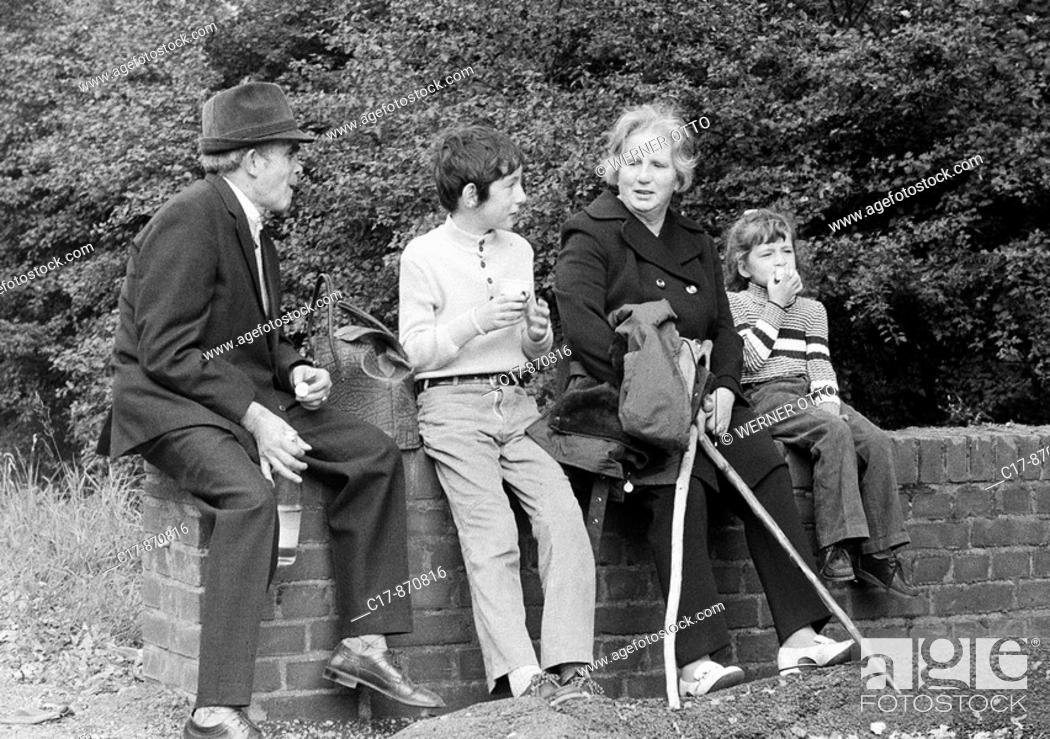 Stock Photo: Seventies, black and white photo, people, grandparents and two grandchildren take a walk, sitting on a wall and have a rest with a small picnic, grandpa.