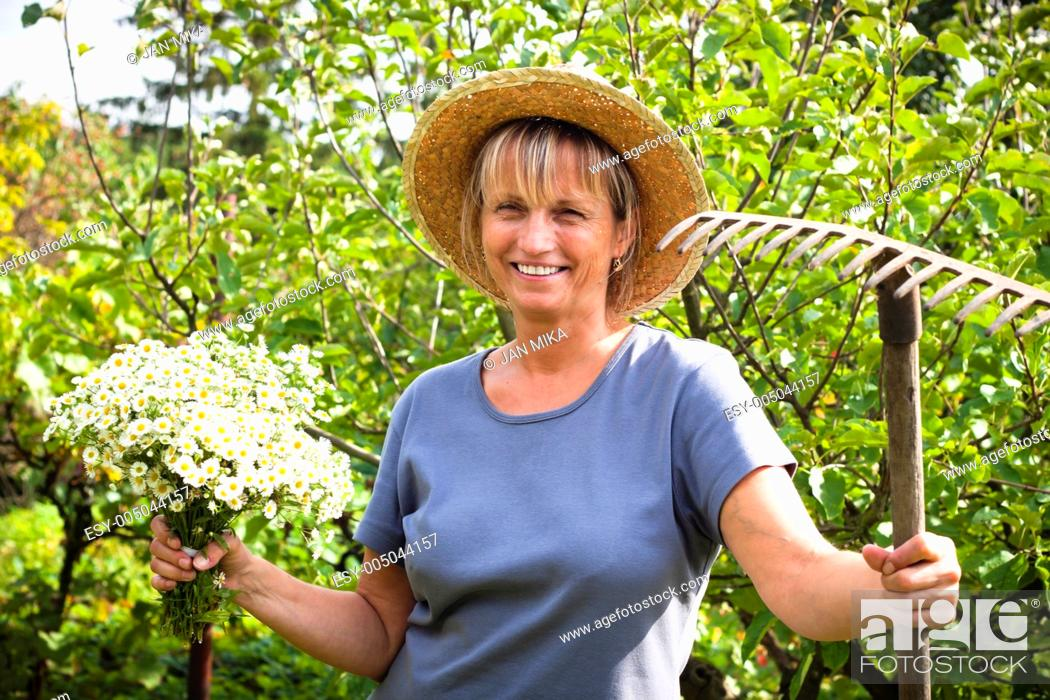 Stock Photo: Portrait of happy mature woman holding flowers and rake in the garden.