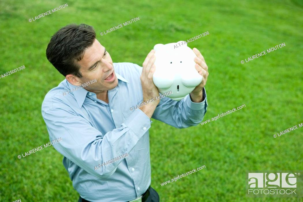 Stock Photo: Man holding piggy bank upside down, looking surprised.
