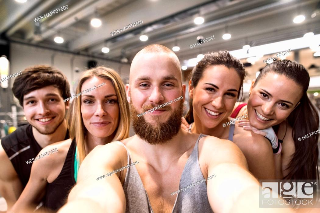 Photo de stock: Young athletes having fun in the gym, taking selfies.