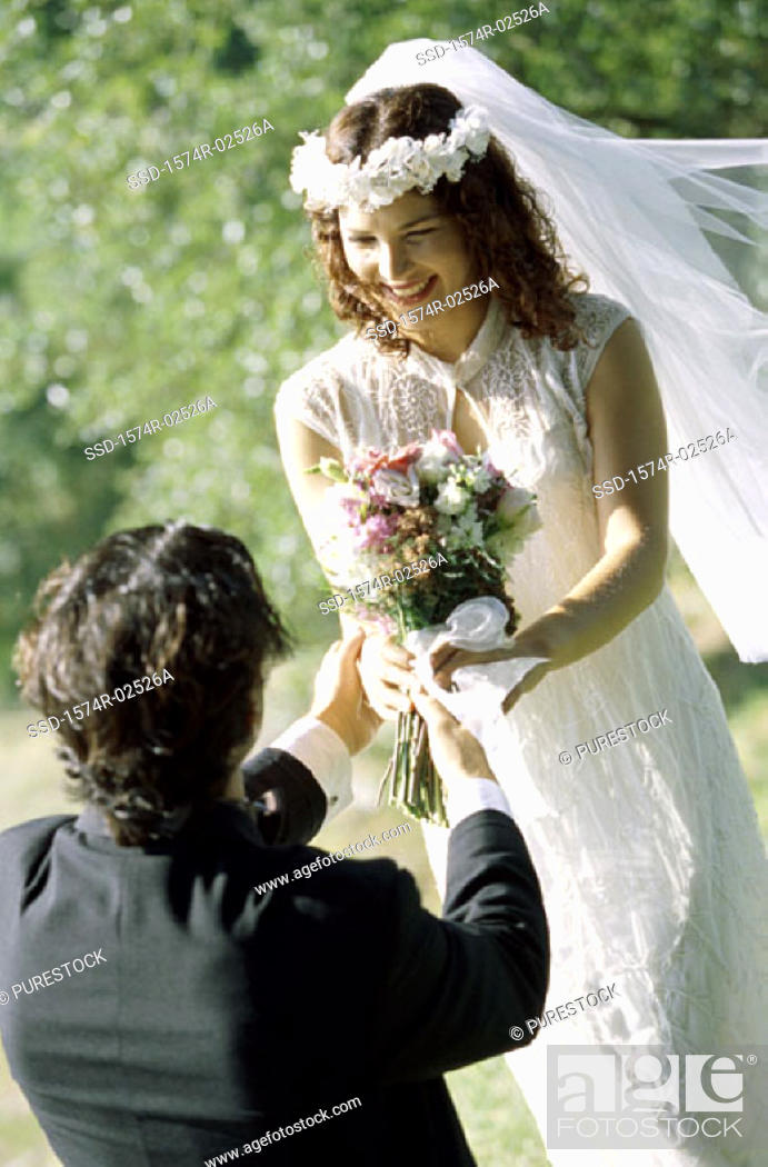 Stock Photo: High angle view of a groom giving a bouquet of flowers to his bride.