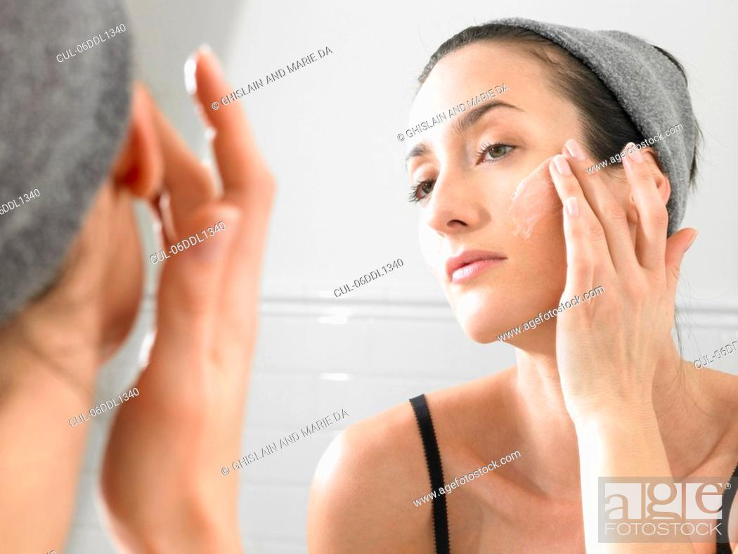 Stock Photo: Woman putting on face cream.