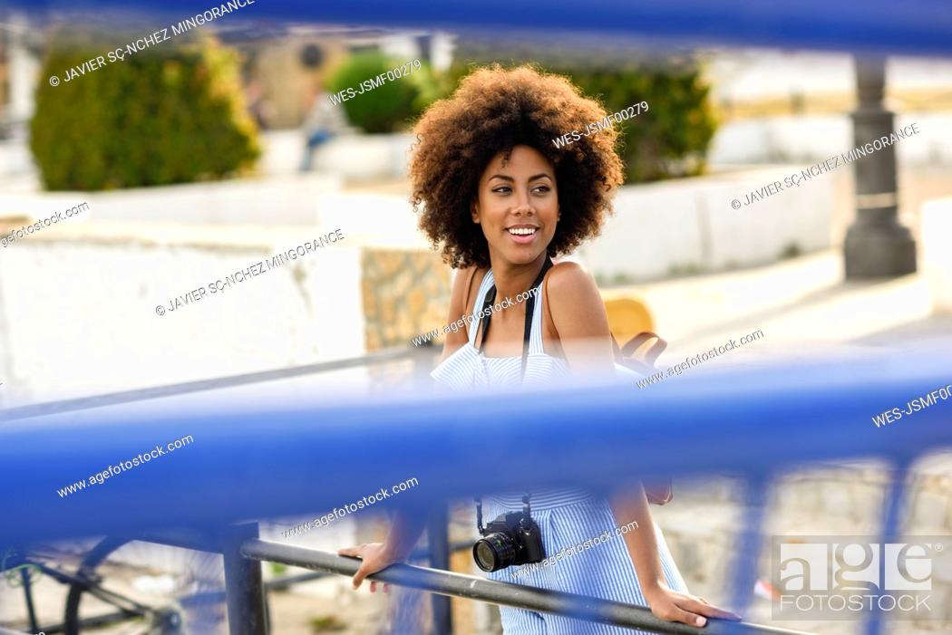 Stock Photo: Portrait of smiling young woman with curly hair on a bridge.